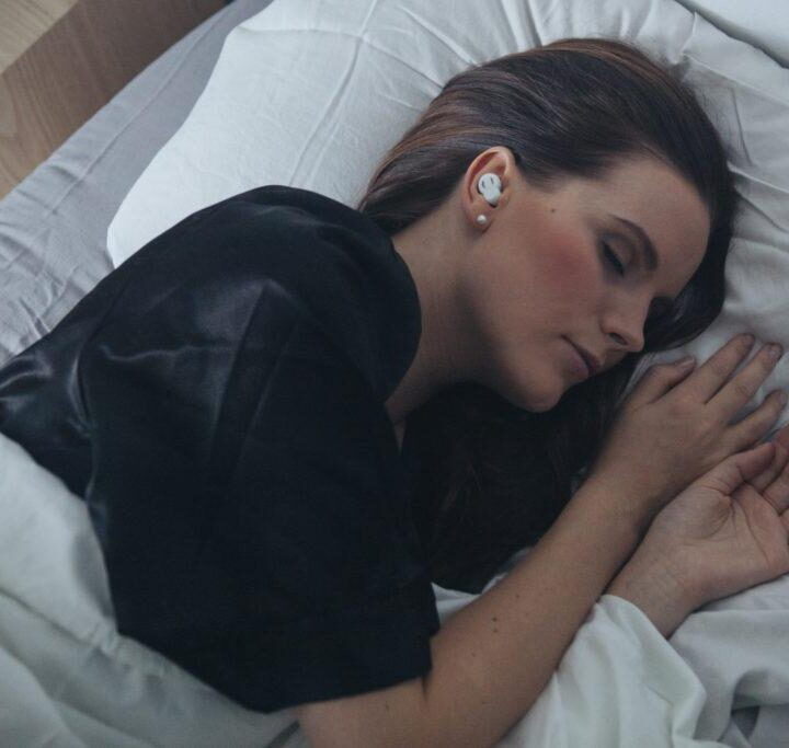 Person sleeping with QuietOn noise cancelling headphones