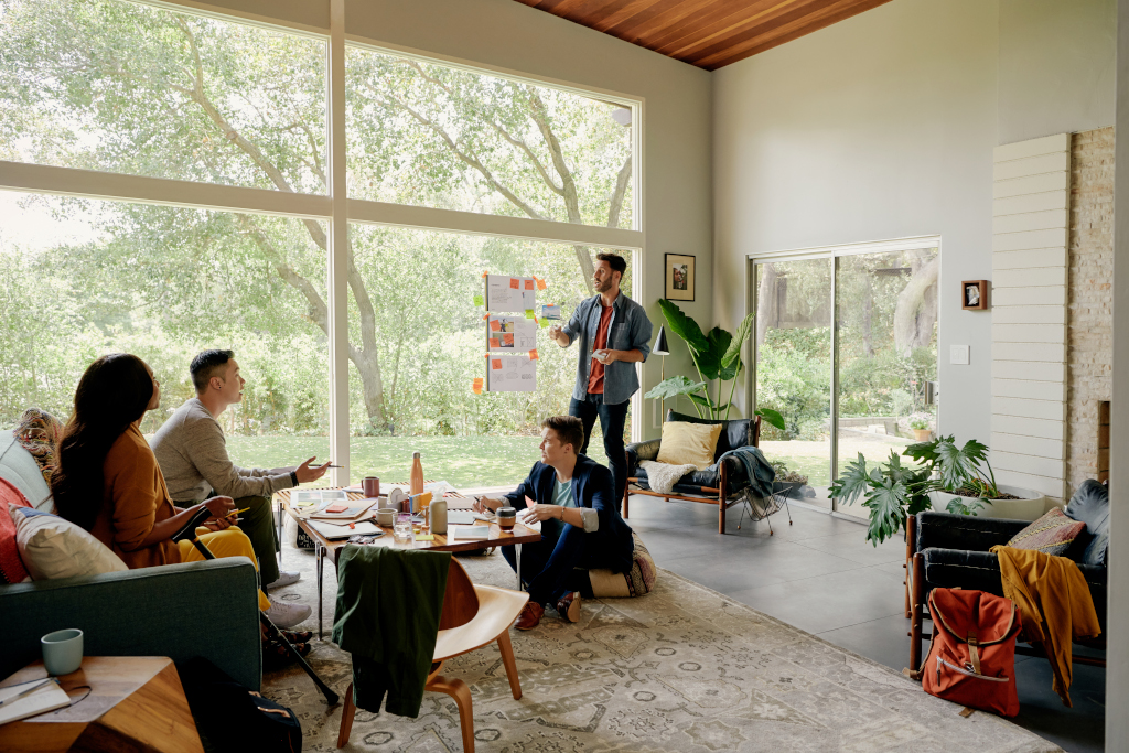 People having a business meeting in a home provided by Airbnb, as one of the examples of great employee experience